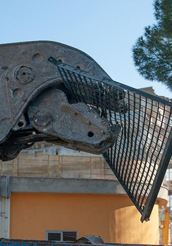 Braccio meccanico durante la demolizione della palazzina