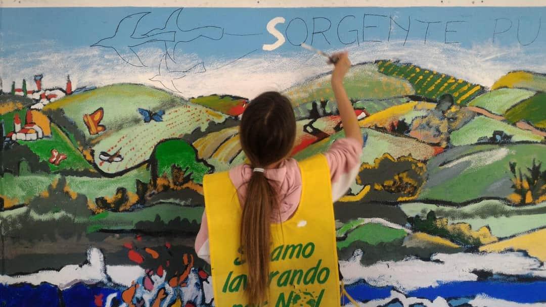 Una bambina dipinge un murale, tema la consapevolezza ambientale